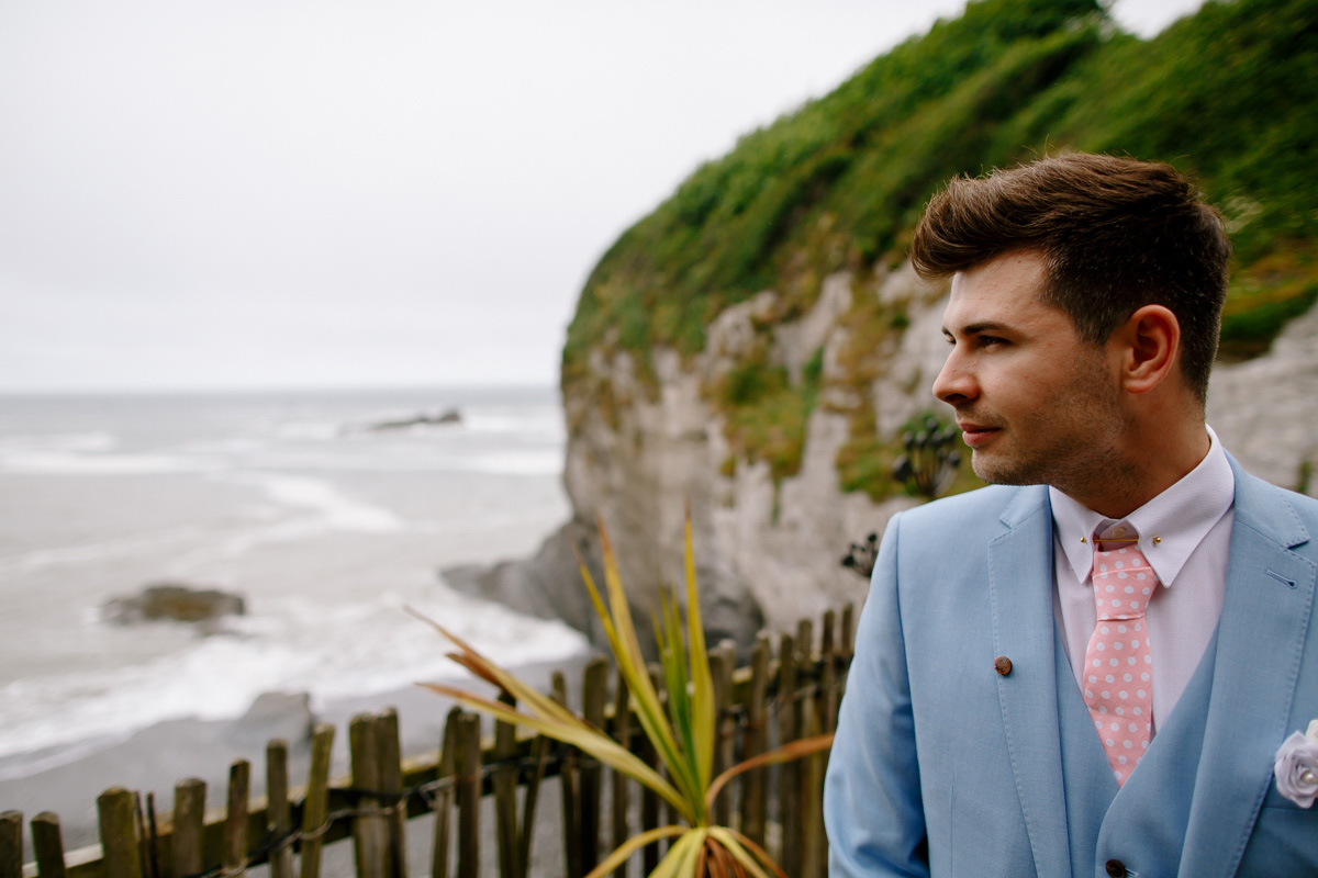 Groom looks out at the coast before his Tunnels beaches wedding