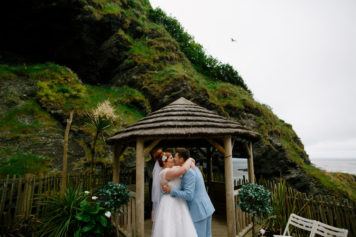 the bride and groom kiss after their ceremony at tunnels beaches