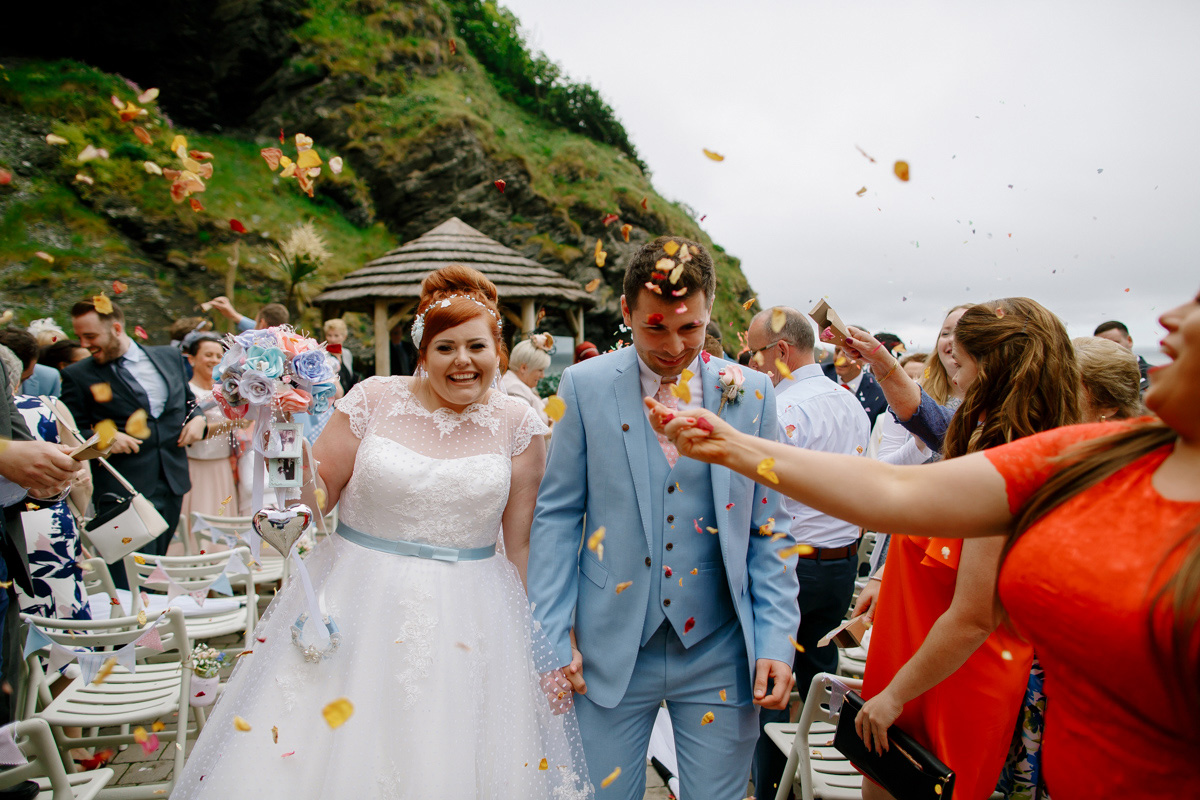 bride and groom showered in confetti as they walk back up the aisle