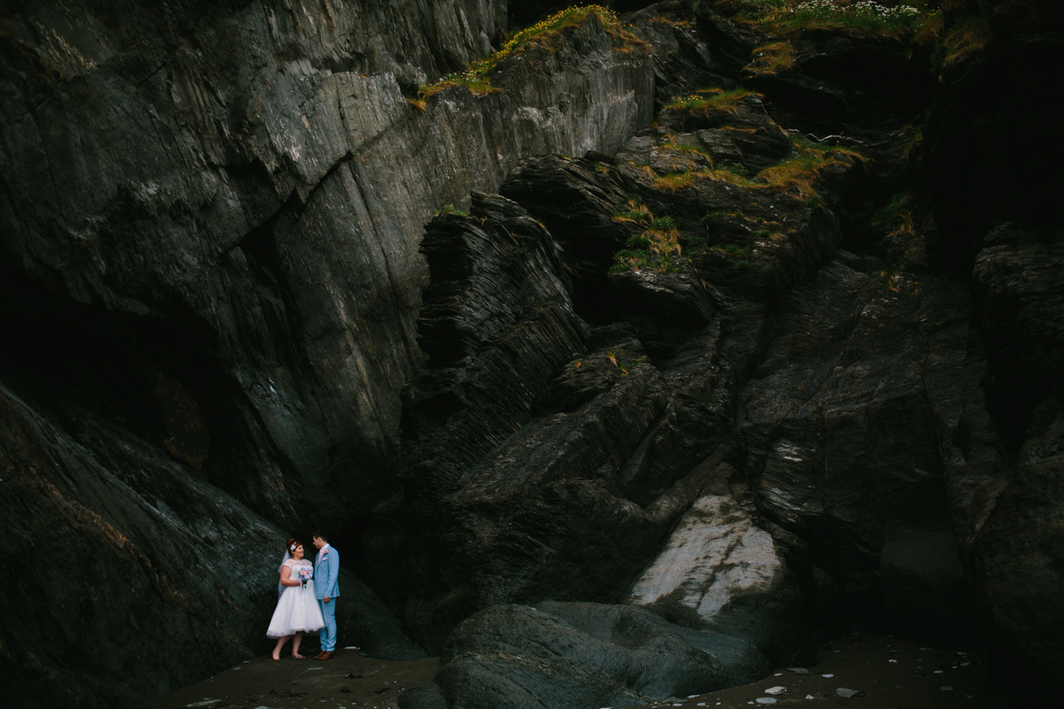 the bride and groom posing on the beach at the tunnels in Ilfracombe