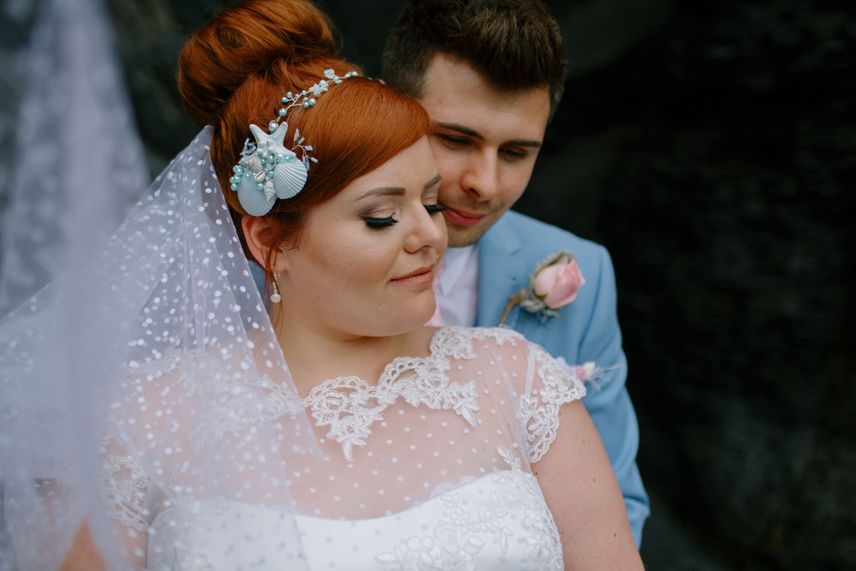 bride and groom embrace during their wedding portraits