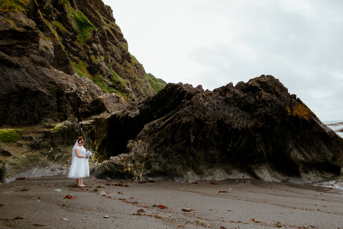 bride stood alone on the beach at her wedding venue in Ilfracombe