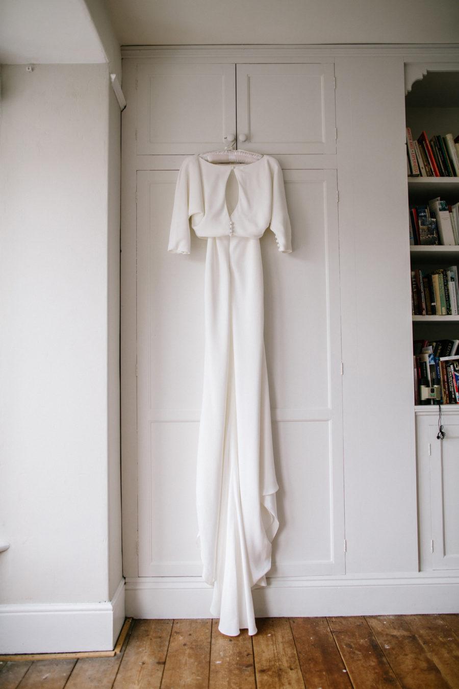 brides dress hangs in her bedroom of her wedding day