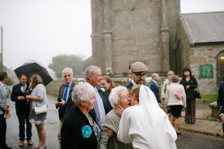 guests greet the bride outside church in Cornwall