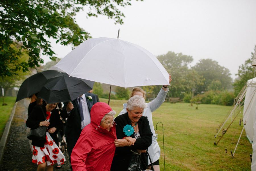 wedding guests huddle from cornish mizzle under an umbrella