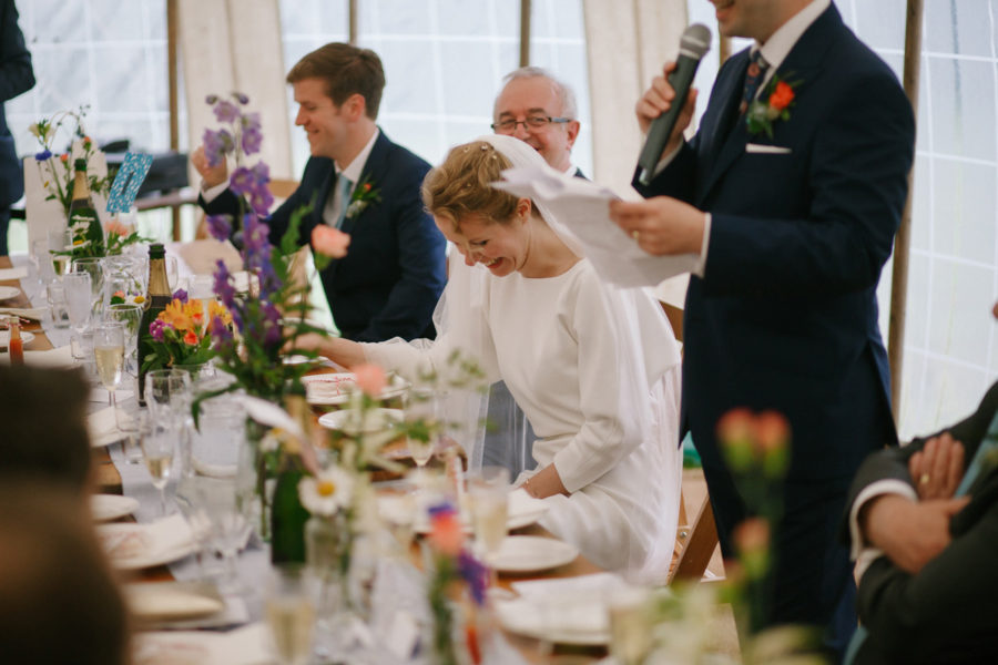 bride laughing at grooms speech at her wedding