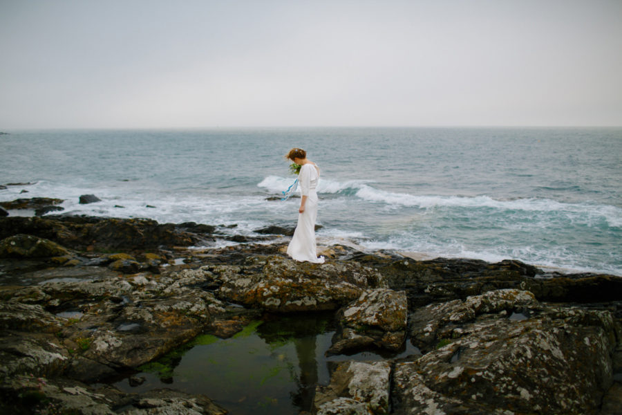 cornish bride standing on rocks looking out to sea