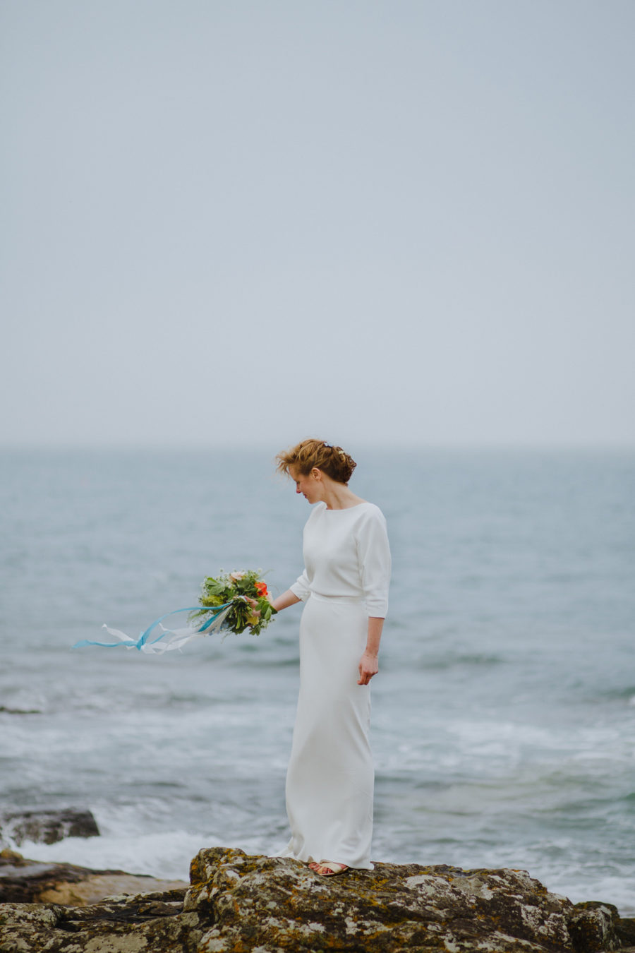 stunning bride stands on the rocks at Mousehole in Cornwall