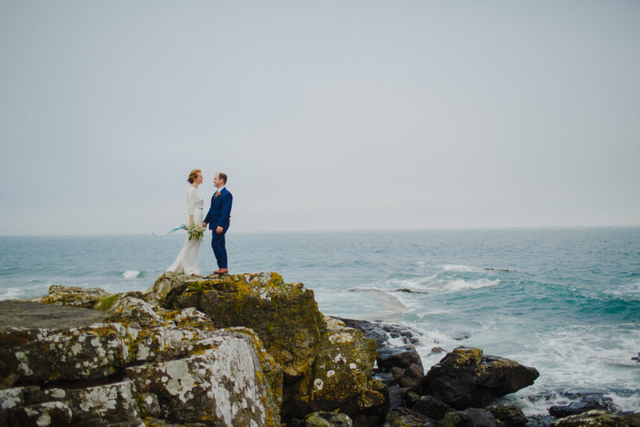 bride and groom holding hands by the sea in Cornwall