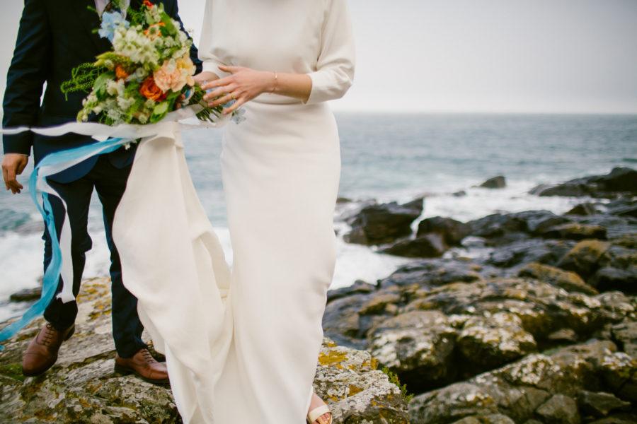 beautiful wedding dress blowing in the wind on the cornish coast