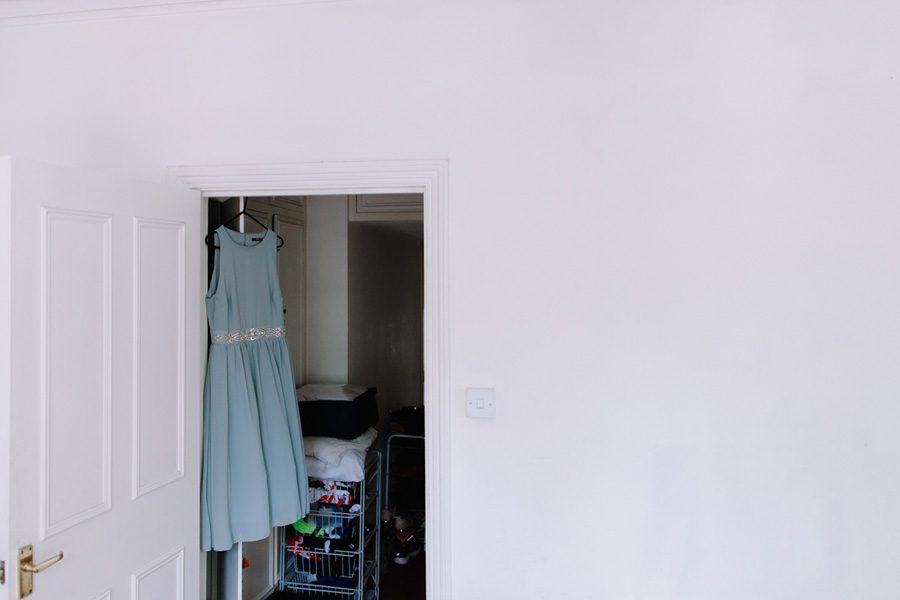 Bridesmaids dress hanging in a doorway
