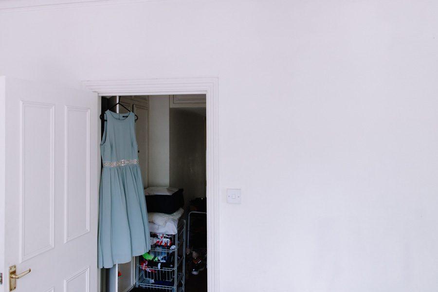 Bridesmaids dress hanging in a doorway