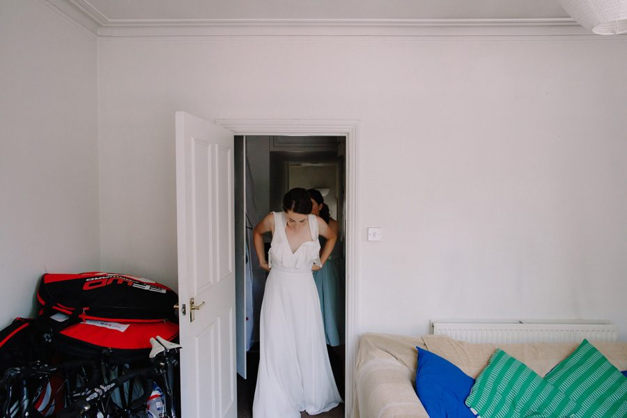Bride puts on her dress from Whistles for her intimate london wedding