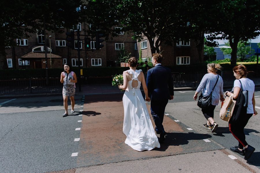 bride and groom cross a london street hand in hand before their wedding