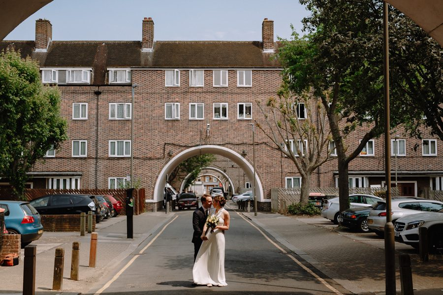 Bride and groom pose on the Henry Prince Estate in Wandsworth