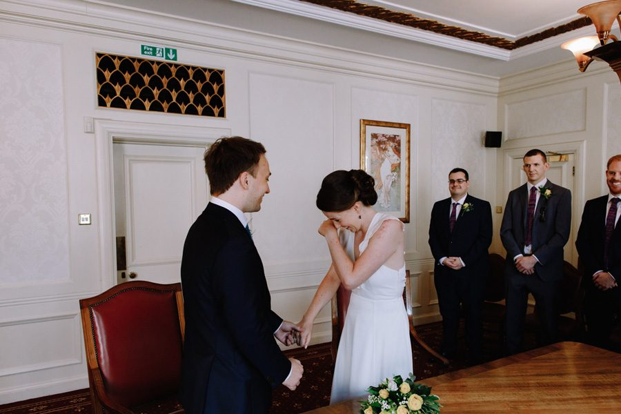 The bride wipes away a tear at her intimate London wedding