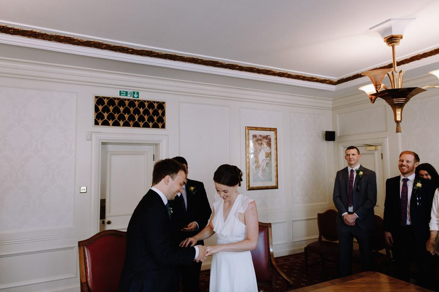 bride and groom exchange rings at their wandsworth town hall wedding
