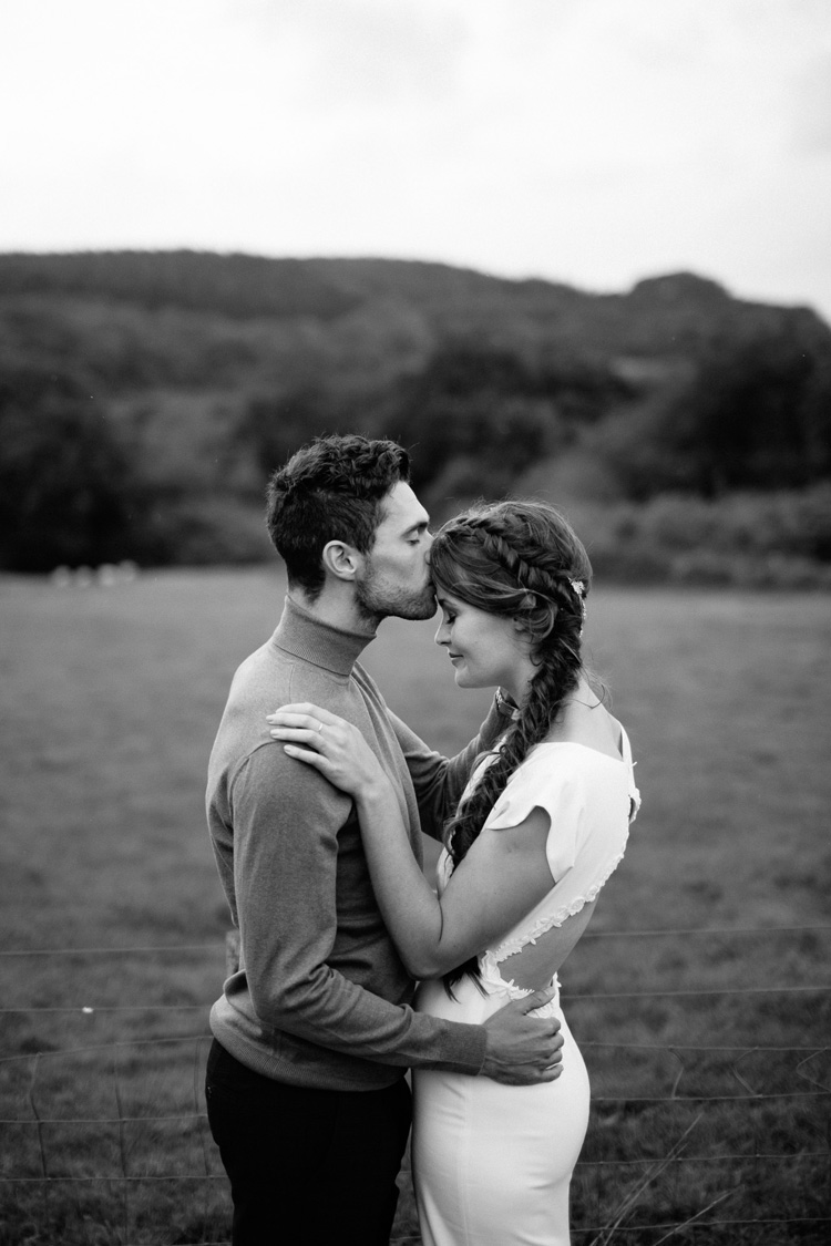 the bride and groom share a kiss in front of beautiful Devon countryside