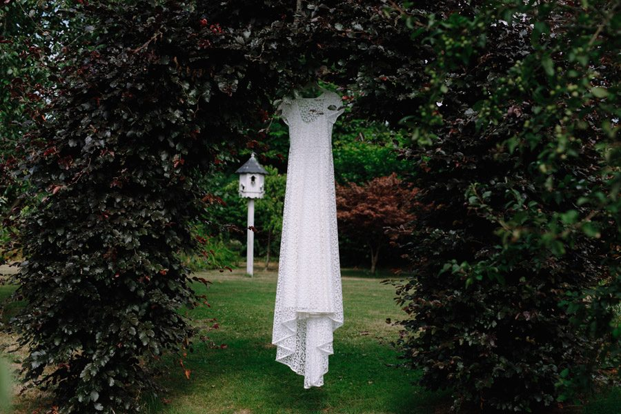 Brides dress hanging in a beautiful garden