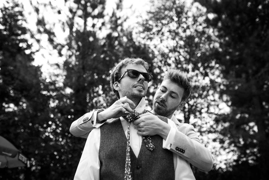 Groom being helped to dress by a groomsman