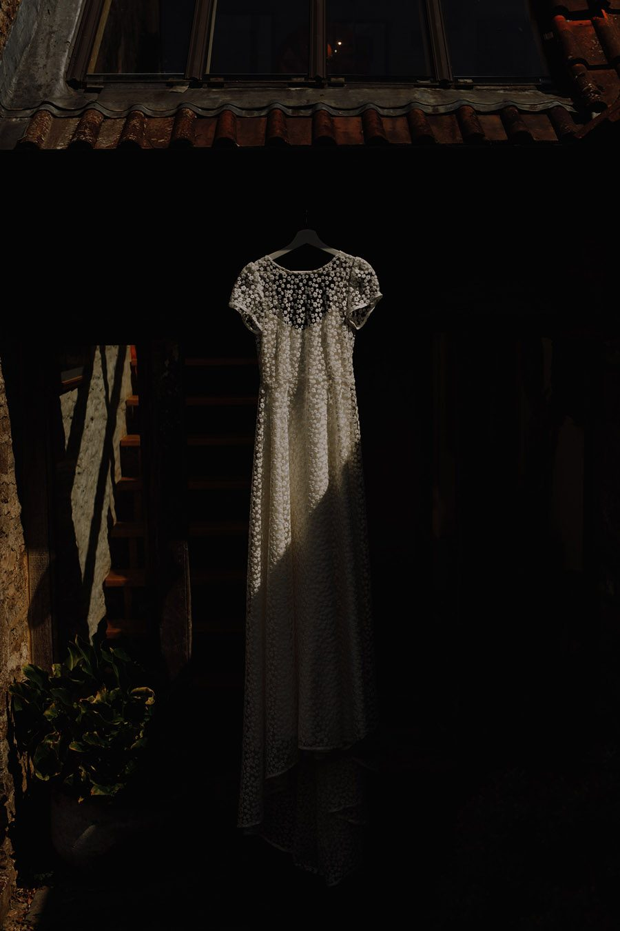 wedding dress hanging in the shadows of a house