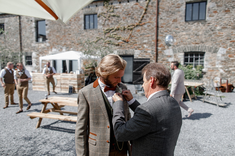 Groom fitting buttonhole onto his suit