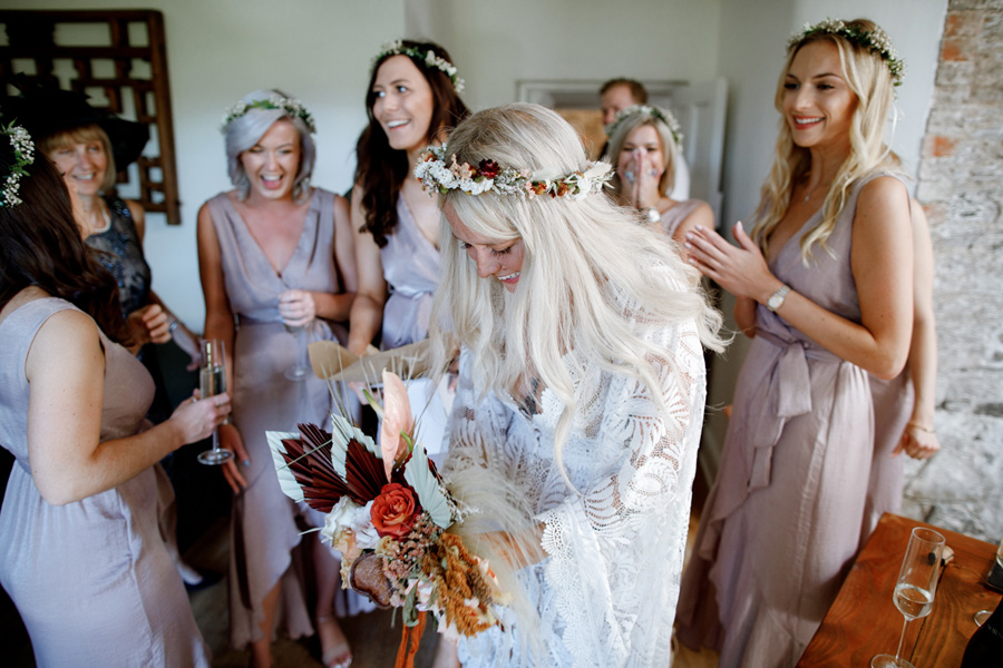 bride wipes away a tear of joy as bridesmaids cheer