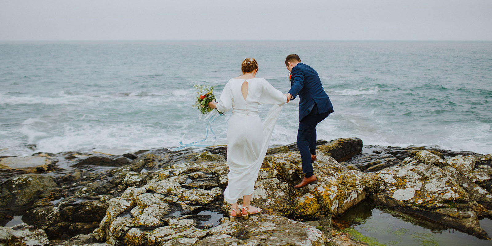 bride and groom on the rocks at Mousehole in Cornwall after their wedding