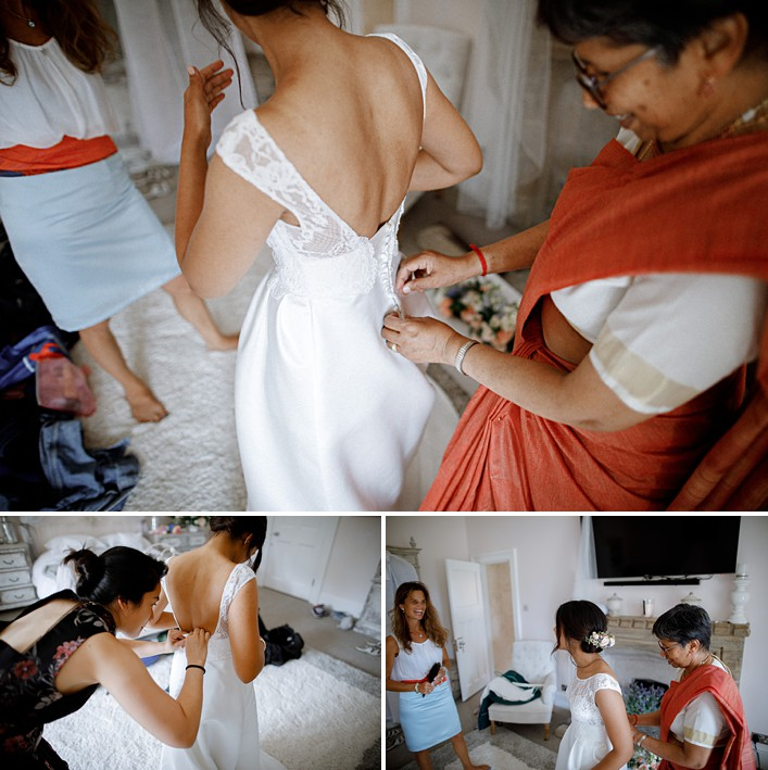 brides mum helps her into her wedding dress